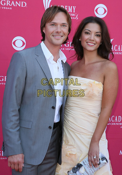 BRYAN WHITE & ERICA PAGE WHITE.The 43rd Annual Academy of Country Music Awards (ACM) held at MGM Grand Garden Arena, Las Vegas, Nevada, USA..May 18th, 2008.half length grey gray suit jacket strapless dress peach orange cream corsage flower .CAP/ADM/MJT.© MJT/AdMedia/Capital Pictures.