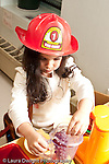 Education preschool 3-4 year olds girl wearing fire hat playing in ktichen area with toy food fruit and container vertical