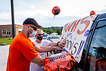 WATERTOWN, CT. 04 June 2020-060420BS227 - Watertown coaches, assistant coach Mark Zaborowski, left, and head coach Timothy Malootian, right, apply a sign to a car as they get ready to honor the Watertown Girls Tennis Team's seniors by driving by each of their homes in a Girls Tennis Team car parade on Thursday. Bill Shettle Republican-American