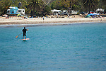 Paddle board enthusiast in bay on the California coast with campgound in background