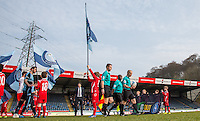 Referee Andy Woolmer leads the teams out past a 'Kick it Out' Banner during the Sky Bet League 2 match between Wycombe Wanderers and Stevenage at Adams Park, High Wycombe, England on 12 March 2016. Photo by Andy Rowland/PRiME Media Images.