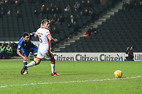 Andy Barcham of AFC Wimbledon shoots as Scott Wootton of MK Dons looks on during the Sky Bet League 1 match between MK Dons and AFC Wimbledon at stadium:mk, Milton Keynes, England on 13 January 2018. Photo by David Horn.