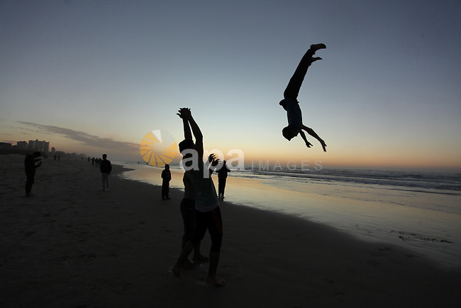 Palestinians enjoy on the beach of Gaza City, during the last sunset of 2016, on December 31, 2016. Photo by Ashraf Amra