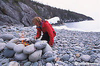 Woman building a fire among smooth beach rocks at the lakeshore