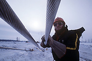 Quebec, Canada, February 1980.   The James Bay Project, a series of hydroelectric power stations on the La Grande River in northwestern Quebec, Canada, built by the state-owned utility Hydro-Quebec.  The project covers an area of the size of the State of New York and is one of the largest hydroelectric systems in the world, with a generating capacity of 16,527 megawatts. Men were working in extreme weather conditions to install and stretch the power electric line. Hydro-Quebec sell his electricity to United States.