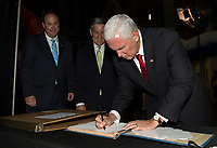 In this photo released by the National Aeronautics and Space Administration (NASA) United States Vice President Mike Pence signs a NASA Kennedy Space Center (KSC) guest book while Acting NASA Administrator, Robert Lightfoot, left, and KSC's director, Robert D. Cabana, center, look on, Thursday, July 6, 2017, in the green room at KSC in Cape Canaveral, Florida. Vice President Mike Pence is scheduled to speak at the event to highlight innovations made in America and tour some of the public/private partnership work that is helping to transform the center into a multi-user spaceport. Photo Credit: Aubrey Gemignani/NASA/CNP/AdMedia