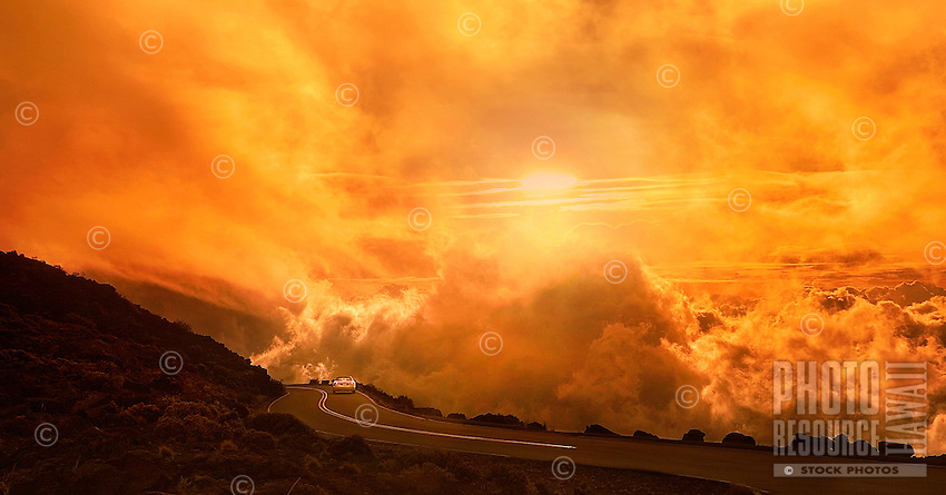 A car driving the scenic winding road down Haleakala into a dreamy, cloudy atmosphere at sunset.