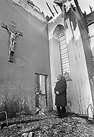 Roman Catholic Bishop of Down and Connor, Dr Patrick Walsh, stands inside the burnt-out remains of the Church of the Virgin Mary and Saint Brigid, Magheranesk, near Glenavy, Co Antrim, N Ireland, UK, burnt in a secterian attack, November 1991. 199111234. <br />