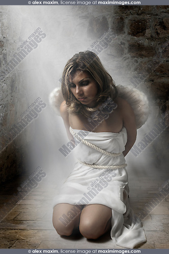 Young woman with angel wings sitting on the floor of a stone cell tied with ropes