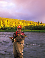 Fly fisherman with rainbow trout on Gulkana River, Alsaka