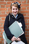Model released portrait of teenage school girl with her art folders standing against brick wall