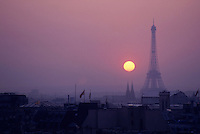 Silhouette of the Eiffel Tower surrounded by rooftops at sunset, Paris, France.