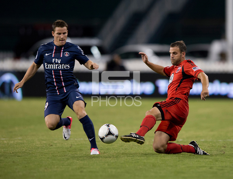 Kevin Gameiro (19) of Paris Saint-Germain FC fights for the ball with Daniel Woolard (21) of D.C. United during the game at RFK Stadium in Washington, DC.  Paris Saint-Germain FC tied D.C. United, 1-1.