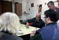 "Pictured: Railway employees play card games during a break at the OSE freight depot in Thessaloniki, Greece. Panayiotis (C) who has worked there for 33 years, has witnessed many that have been returned by the border authorities. ""I once witnessed a Syrian woman holding her young child, attempting to enter a train container that was previously used to carry diesel fuel"".  Wednesday 05 April 2017<br /> Re: A year after an agreement was signed between Greece and Turkey for the management of refugees. Migrants, mostly from Morocco, Algeria and Tunisia, have been living in disused train carriages at the Thessaloniki freight depot of OSE in northern Greece, the company managing the railways in the country. Some of the migrants climb onto moving trains, or even hide themselves in storage areas, hoping that they will cross the border."