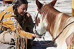 A Native American Indian woman feeding a friends horse when they get together