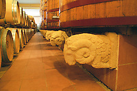 Oak barrels and big foudre fermentation vats in the winery, the plinth decorated with the winery symbol the boar, Chateau Puech-Haut, Saint-Drezery, Coteaux du Languedoc, Languedoc-Roussillon, France