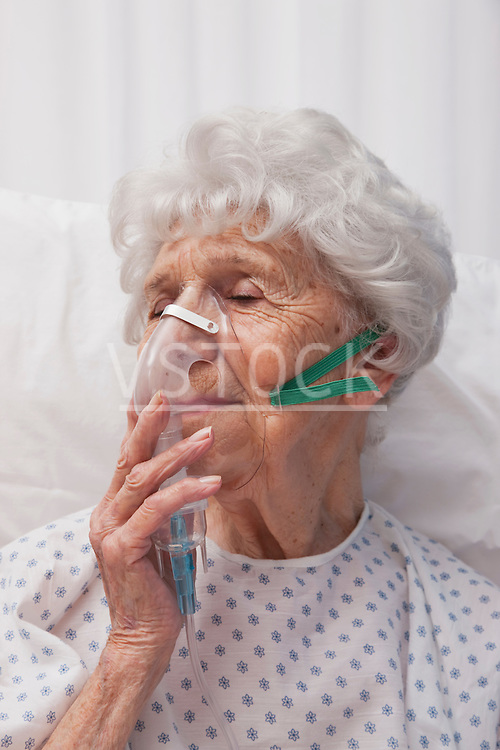 USA, Illinois, Metamora, Senior woman with oxygen mask lying in hospital bed