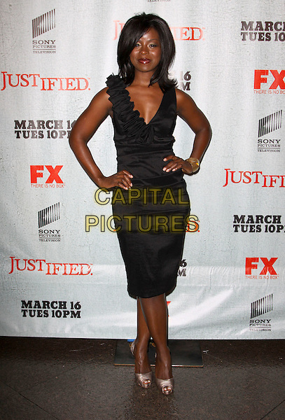 "ERICA N. TAZEL.FX's ""Justified"" - Los Angeles Premiere Screening held At The Director Guild Of America, West Hollywood, California, USA..March 8th, 2010.full length black sleeveless dress hands on hips ruffle.CAP/ADM/KB.©Kevan Brooks/AdMedia/Capital Pictures."