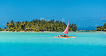 Red boat saling in Bora Bora lagoon, French Polynesia