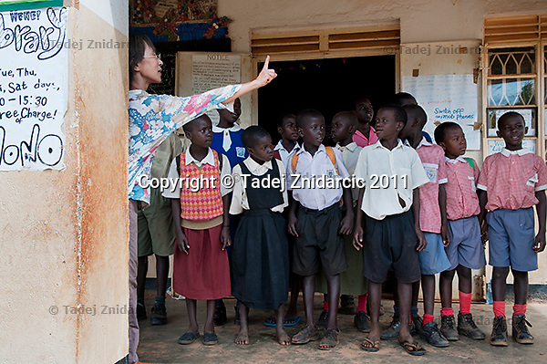 NGO worker from Japan instructs pupils during rehearsals for Book Day Celebration at the Kitgum library, Kitgum Town, Kitgum District.