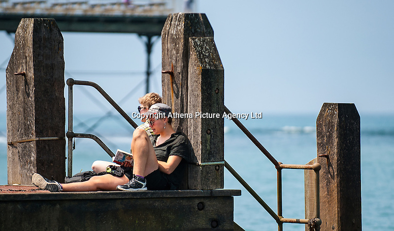 HOT WEATHER WALES Aberystwyth, Ceredigion, West Wales. UK Weather Wednesday  8th June 2016: With yellow warnings for rain across swathes of England the sun comes out at lunchtime with temperatures reaching 19 degrees celsius after a dull morning. Two women relax whlst reading on the wooden jetty on the seafront.