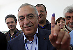 Palestinian Prime Minister Salam Fayyad casts his vote for the municipal elections at a polling station in the West Bank village of of Deir al-Ghusun north of Tulkarm, on October 20, 2012. Palestinians in the West Bank voted in local elections in what was the first time they had gone to the polls since 2006. Photo by Mustafa Abu Dayeh