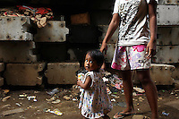 A young girl with her father in a central Jakarta slum.<br />