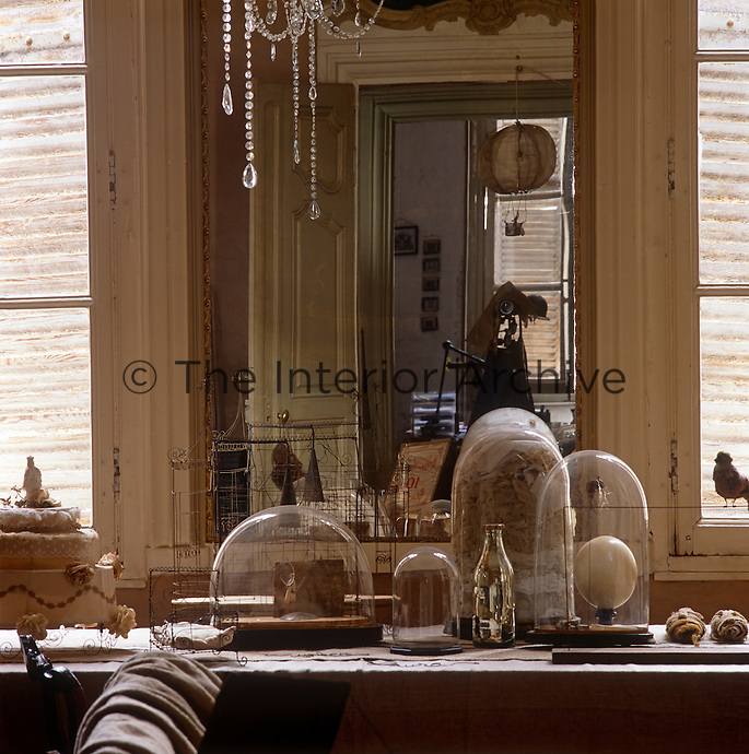 Glass domes are arranged on a table in front of a mirror set in a panelled wall.
