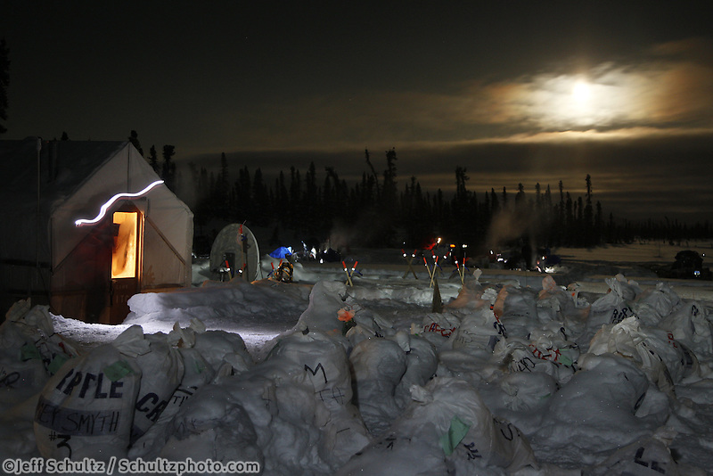 Friday March 9, 2012  the Communications tent is lit up and surrounted by mushers food drop bags as a full moon lights the sky of  the half-way checkpoint at Cripple.   Iditarod 2012.