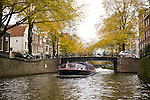 A canal boat guides tourists on a tour in Amsterdam, the Netherlands. In the background, the yellow autumn colors.