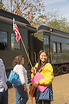Essex, CT Steam Train excursion. Asian tourist with american flag.