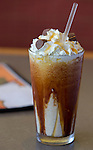 A milk shake with chocolate and whipped cream.