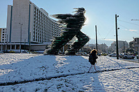 Pictured: A young woman walks by the Runner (Dromeas) statue by the Hilton Hotel in Central Athens, Greece. Tuesday 08 January 2018<br /> Re: Heavy snowfall has affected most parts of Greece.