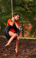 "Alex Craft, 12, rides the tireswing in front of her Anderson home Wednesday. Alex, who was out enjoying the warm weather after getting out of school early, said she enjoys twirling on the swing. ""You just run and jump and you go round and round,"" she said."