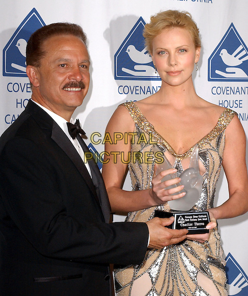 GEORGE R. LOZANO & CHARLIZE THERON.Attends Covenant House California's Covenant with Youth Awards Dinner Gala and she is honored for her outstanding contribution to the lives of at risk & homeless youth held at The Beverly Hills Hotel in Beverly Hills, California .May 7,2004.half length, half-length, award, trophy.www.capitalpictures.ccom.sales@capitalpictures.com.©Capital Pictures.
