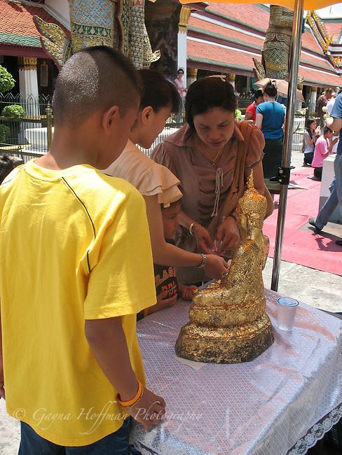 Mother and children making an offering.Wat Phra Kaew, Bangkok, Thailand