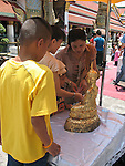 Mother and children making an offering.Wat Phra Kaew, Bangkok, Thailand