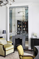 A floor-to-ceiling mirror with industrial style exposed rivets surrounds the fireplace of this Claridges hotel suite