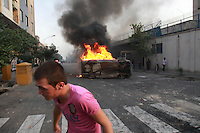Demonstrators on Khosh Street beside a burning car. Following a disputed election result, thousands of supporters of opposition candidate Mir-Hossein Mousavi took to the streets in protest.