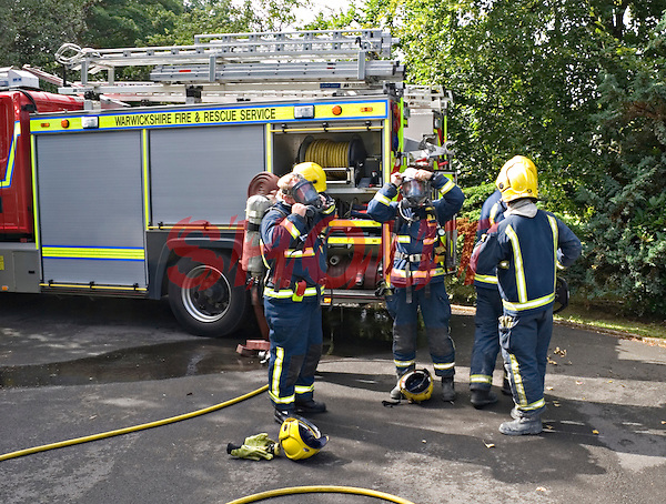 Firefighters prepare to wear Breathing Apparatus to enter a home to deal with a severe fire. This image may only be used to portray the subject in a positive manner..©shoutpictures.com..john@shoutpictures.com