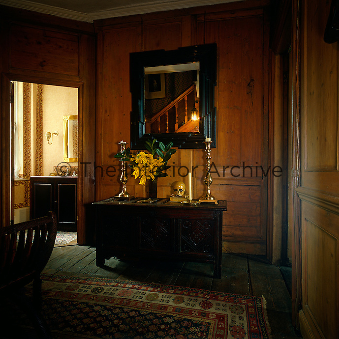 The dark wood-panelled staircase hall of this Georgian house with the balustrade of the stairs reflected in the mirror