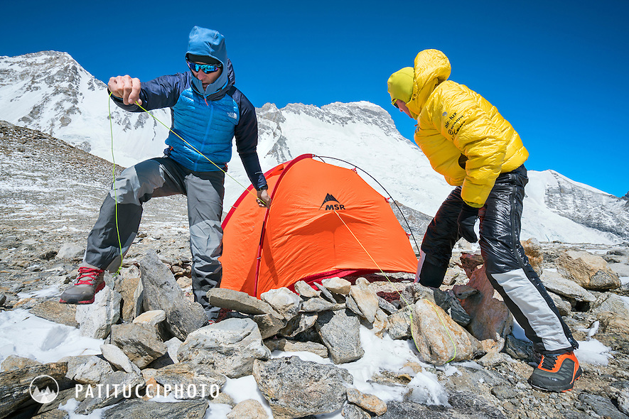 Ueli Steck and David Göttler seting up a tent in very windy conditions at advance basecamp during a climbing expedition to the 8000 meter peak Shishapangma, Tibet