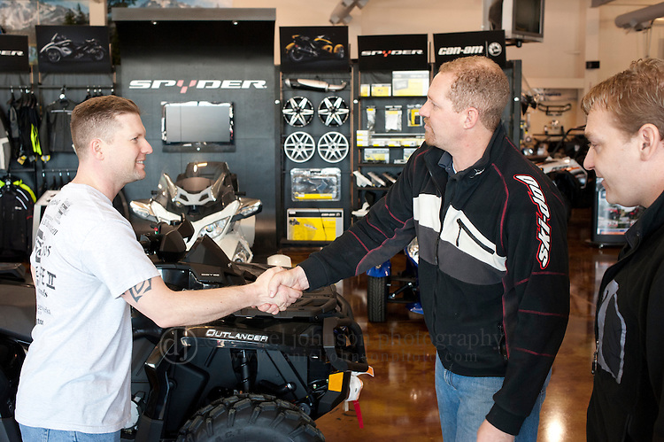 16 February 2012 --  Can-Am ATV Giveaway. Jason Moore of Omaha, left, greets Bob Smith of Leisure Life Sports, center, and BRP Sales Representative Aaron Clayton as Moore picks up his Can-Am ATV that he won as prize in Can-Am 4x4x4x4 Sweepstakes. Moore picked up his ATV at Leisure Life Sports in Omaha, Neb.. Picture by Daniel Johnson (Copyright 2012 Daniel Johnson)