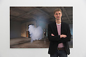 """Pictured: Dutch artist Berndnaut Smilde stands in front of his artwork Nimbus Thor, 2014. Ronchini Gallery London present """"Antipode"""", an exhibition of new works by Dutch artist Berndnaut Smilde. Berndnaut Smilde makes multidisciplinary work through the synthesis of photography, installation, performance and sculpture. 11 April 10 14 June 2014 at the Ronchini Gallery in London."""