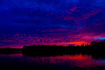 The day's first light reflects off clouds and water's surface at Serpent Lake near Deerwood, Minnesota.