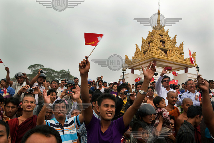 A crowd of supporters wave and cheer a motorcade carrying Aung San Suu Kyi, leader of the National League for Democracy, the country's main opposition party and democracy movement, from Mandalay airport to a field where she is holding a rally during a campaign rally ahead of bi-elections planned for April 2012, in Mandalay.