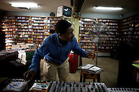 The owner of the Jazz hole, a prominent record store, works on his mixer while talking to a customer  in Nigeria's capital Lagos on Saturday March 28 2009..