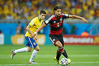 Sami Khedira of Germany goes past Oscar of Brazil