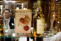 Guests enjoy the food and neighborhood atmosphere at the Miramar vafe in Buenos Aires. The venerable cafe, started as a small grocer early in the last century, is a favorite haunt of the area's tango dancers and culinary aficionados. (Kevin Moloney for the New York Times)