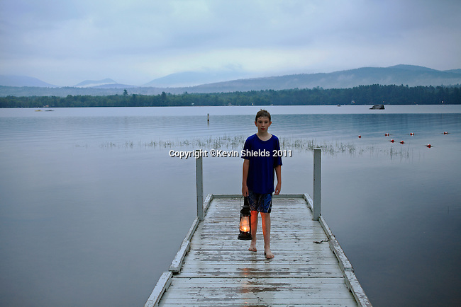 Boy on a boat dock with a lantern at twilight, Mt. Blue State Park, Weld, Maine, USA